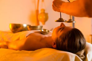 Woman in wellness and spa setting having a singing bowl massage therapy, the therapist is waking her up with cymbals